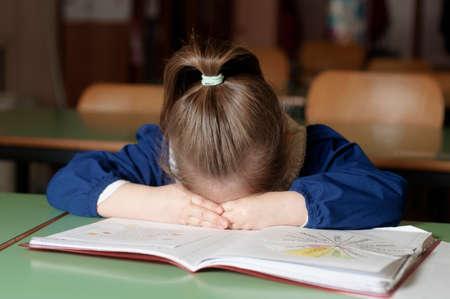 Tired italian elementary school girl (first-grader) sleeping on school desk. Educational and school concept Stock Photo