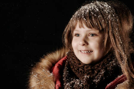 Little caucasian girl in a red coat looking at the falling snow. Snowfall.
