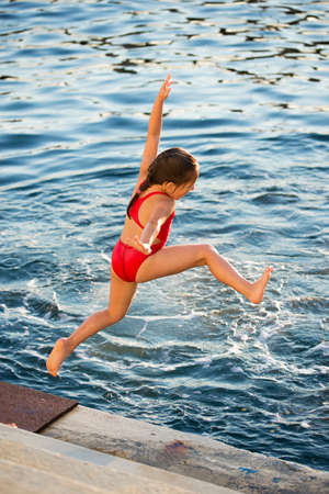 readiness: Little caucasian girl  jumping into the sea