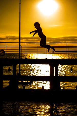 Niña saltando en el mar
