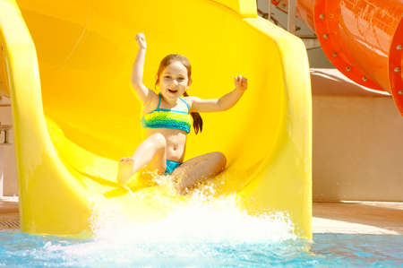 Happy little caucasian girl on waterslide of water park. Stock Photo
