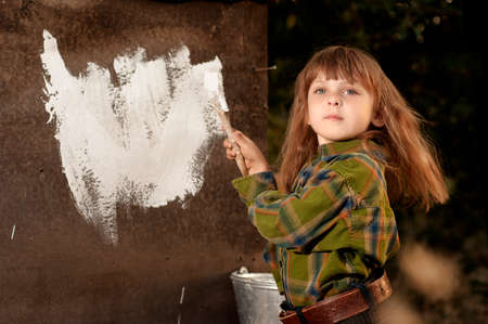 destructed: Little cute caucasian girl colouring a wall of an old destructed house
