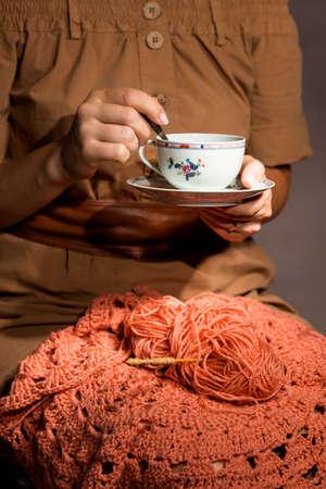 크로 셰 뜨개질과 여자 손을 차 컵. 취미와 레저의 개념.