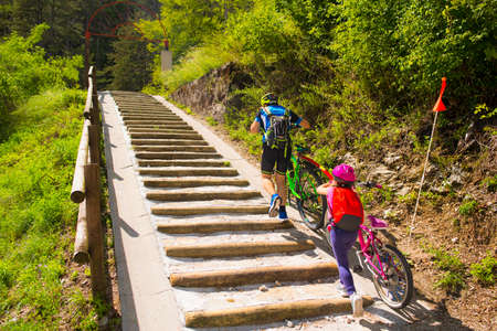 Father and daughter climb the steps with bicycle Stock Photo