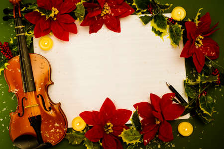 Violin and open music manuscript on the green background. Christmas concept Stock Photo