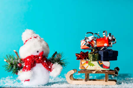 Snowman and sledge with christmas gifts on cyan background Stock Photo