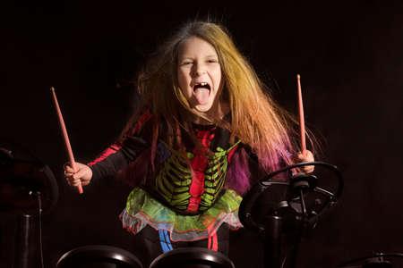 電子ドラムキットを演奏多色の髪を持つ小さな白人の女の子のドラマー 写真素材