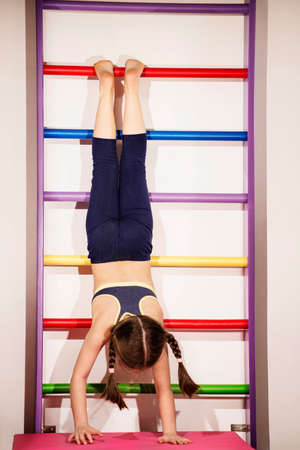 Little caucasian 6-8 years old girlie go up to handstand pose Stock Photo