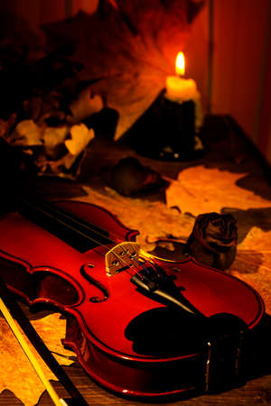 Violin and autumn leaves on the on the table in light of candle in the dark room. Close-up of violin. Focus on the strings. Stock Photo