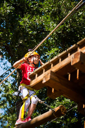 Little brave caucasian girl at outdoor treetop climbing adventure park