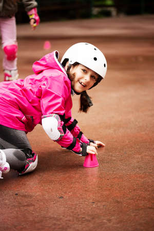 A little caucasian girl beginner roller falling on the ground in the autumn park in the rainy day. Imagens