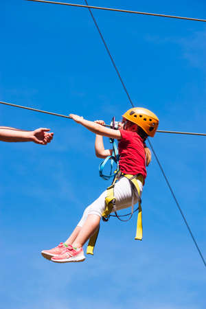 Little brave caucasian girl using a zip line. An indefinited man lend a helping hand.