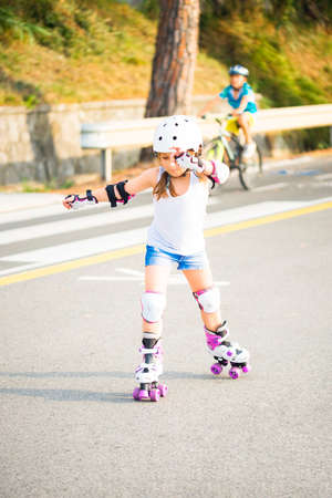 A little caucasian girl with roller quad rolling in the sun summer evening. Rollerblading and outdoor activity concept Stok Fotoğraf