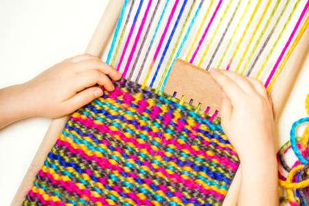 Weaving. Hands of little caucasian girl working on small loom weaving. Standard-Bild - 123952242