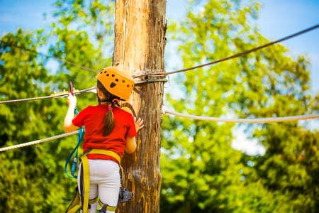 Little brave caucasian girl treerunner fasten the rollclip before climbing Stock Photo