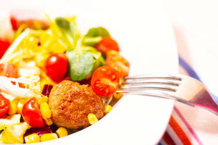 Colorful fresh vegetable salad with meatballs and corn seeds