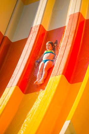 Splash. Little caucasian girl on water slide of water park. Sunny summer day