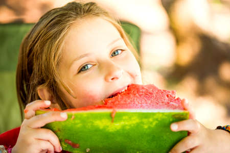 Little caucasian girl eating watermelon in the sunny summer day.