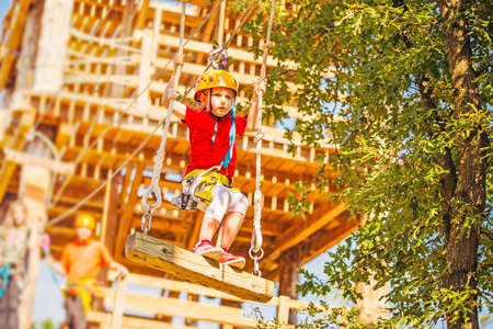 Little caucasian girl using a zip line in a rope playground structure.