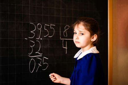 Italian elementary school girl trying to make a long division. The student thinks and feels near the blackboard. Mathematical tasks. Stock Photo