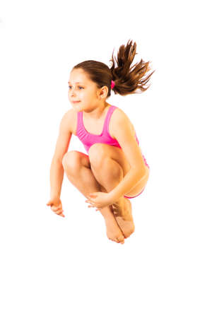 Little caucasian female 8 years old girl in pink swimmwear jumping on white background.