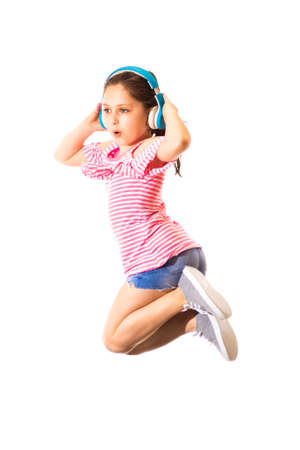 Little funny jumping and shouting little caucasian girl with a headphones