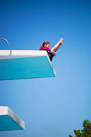 Little caucasian female 8 years old girl in neoprene shorty surfing wetsuit dives from 5 mether diving platform. Stock Photo