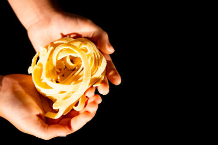 Hands of a little girl holding e fresh home-maded tagliatelle pasta Stock Photo
