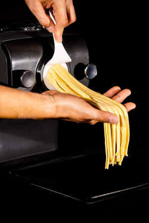 Home made pasta by pasta maker. An indifinited man cutting the tagliatelle. Selected focus