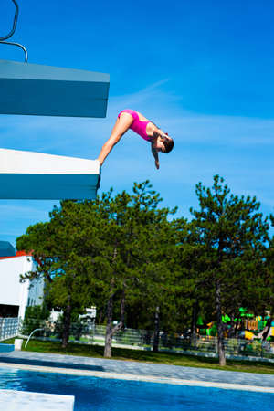 Little caucasian female 8 years old girl diving from diving platform. Summertime, sport and recreation concept.
