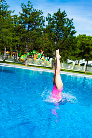 Entrance in the water. Little caucasian female 8 years old girl diving from diving platform. Summertime, sport and recreation concept. Stock Photo