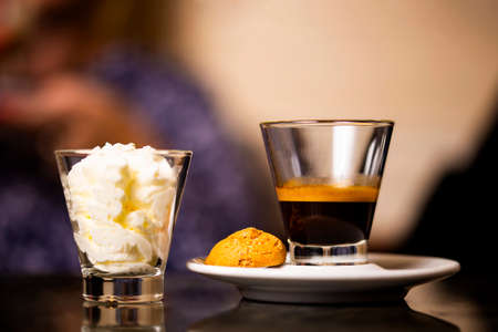 Traditional coffee of Trieste Italy. Black espresso in the glass, with cream and macaroon. Stock Photo