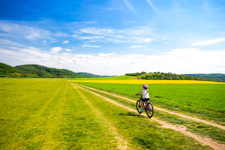 9 years girl going in bicycle across the fields in the sunny day