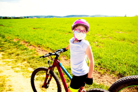 Sport and quarantine. 9 years biker girl in a mask amidst of the fields in the sunny day