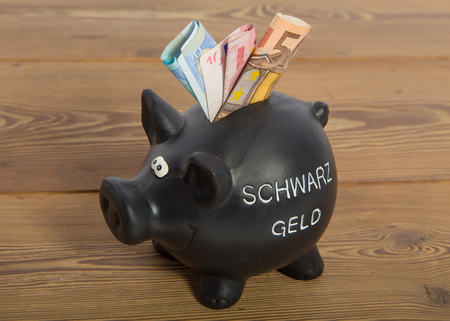 white collar crime: Sparschwein mit Aufdruck Schwarzgeld