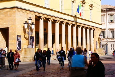 Parma, Italy - September 25, 2012  Group of people, tourists and passers-by, walking relaxedly in front of the Regio Theater, in the historic center of Parma