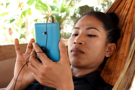 Resting Asian Lady with Mobile Phone photo