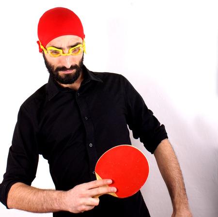pong: Man playing ping pong wearing swimming cap Stock Photo