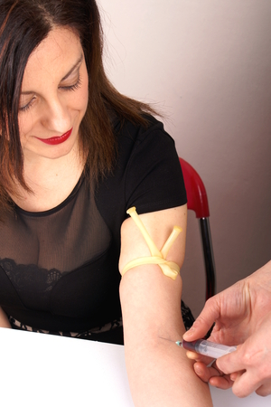 tourniquet: Studio shot of a lady with syringe and tourniquet Stock Photo