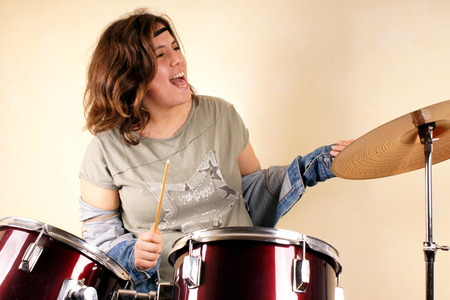 banging: Studio shot of a young lady on drums