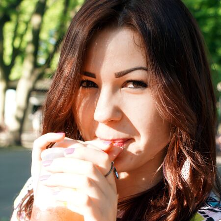 slush: Young lady eating slush in the park Stock Photo