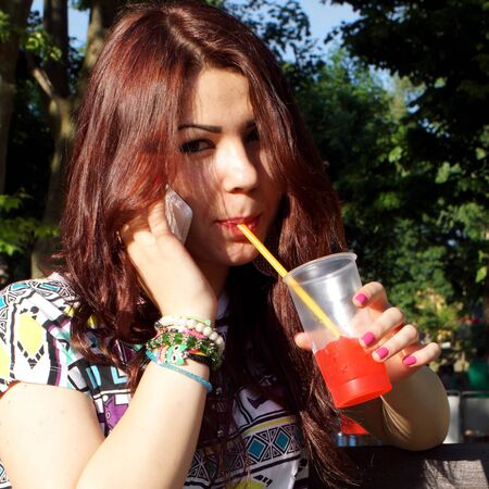 fanghiglia: Young lady eating slush in the park Archivio Fotografico