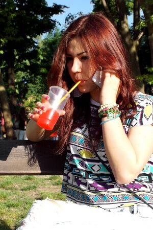 slush: Young lady eating slush in the park Stock Photo