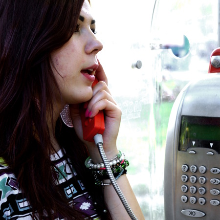 pay phone: Young woman talking on a pay phone