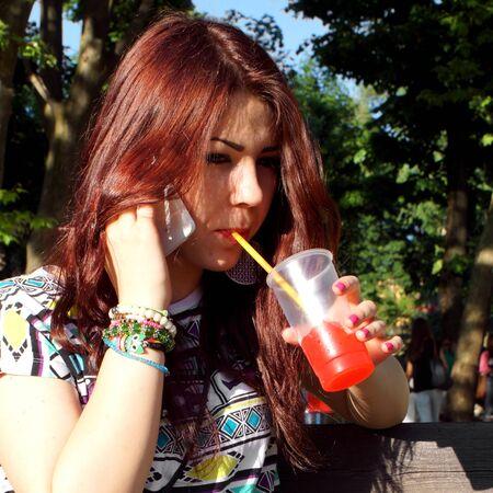 granizados: Señora joven que come aguanieve en el parque