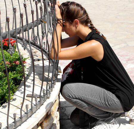virgin girl: Medjugorje, Citluk, Bosnia and Herzegovina - August 12, 2015: A girl praying in front of the Virgin Mary statue of St James church in Medjugorje.