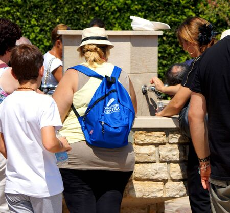 sediento: Medjugorje, Citluk, Bosnia and Herzegovina - August 12, 2015: Thirsty pilgrims take water from the fountain in front of the Church in Medjugorje