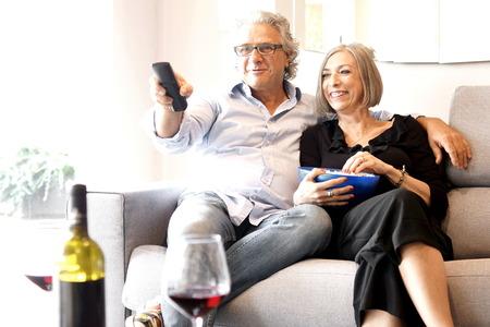 pareja de mediana comiendo palomitas y viendo la televisión Foto de archivo