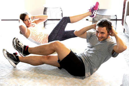 hombre deportista: Una pareja de jóvenes que hacen ejercicio en casa Foto de archivo