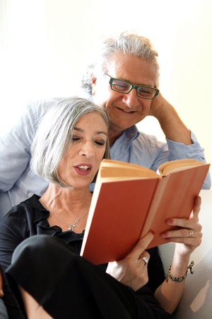 couple on couch: Aged couple reading a book on the couch